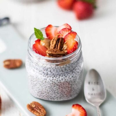 A jar of keto chia pudding with topping suggestions.
