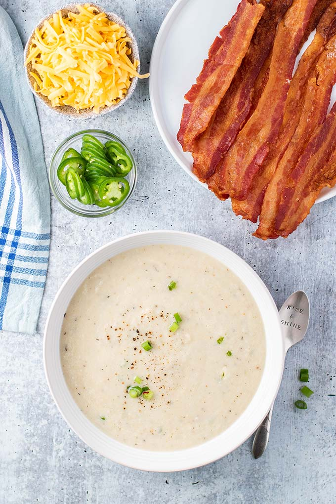 A bowl of creamy keto cauliflower soup, with bacon, cheese, and a bowl of jalapenos sitting next to it.