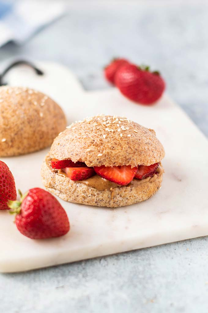 A keto bread roll with almond butter and strawberries.