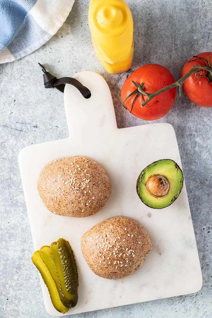 Two keto bread rolls on a cutting board with tomato, pickles, and avocado.