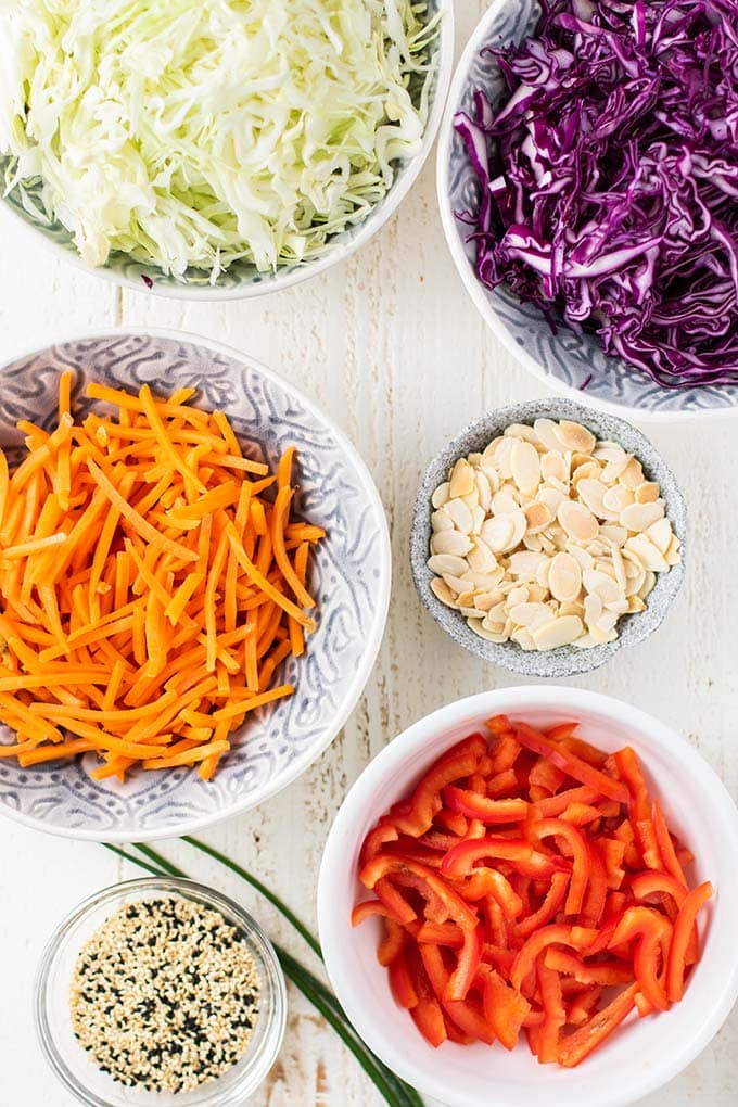 The ingredients for an Asian Chicken Salad prepared and in bowls.