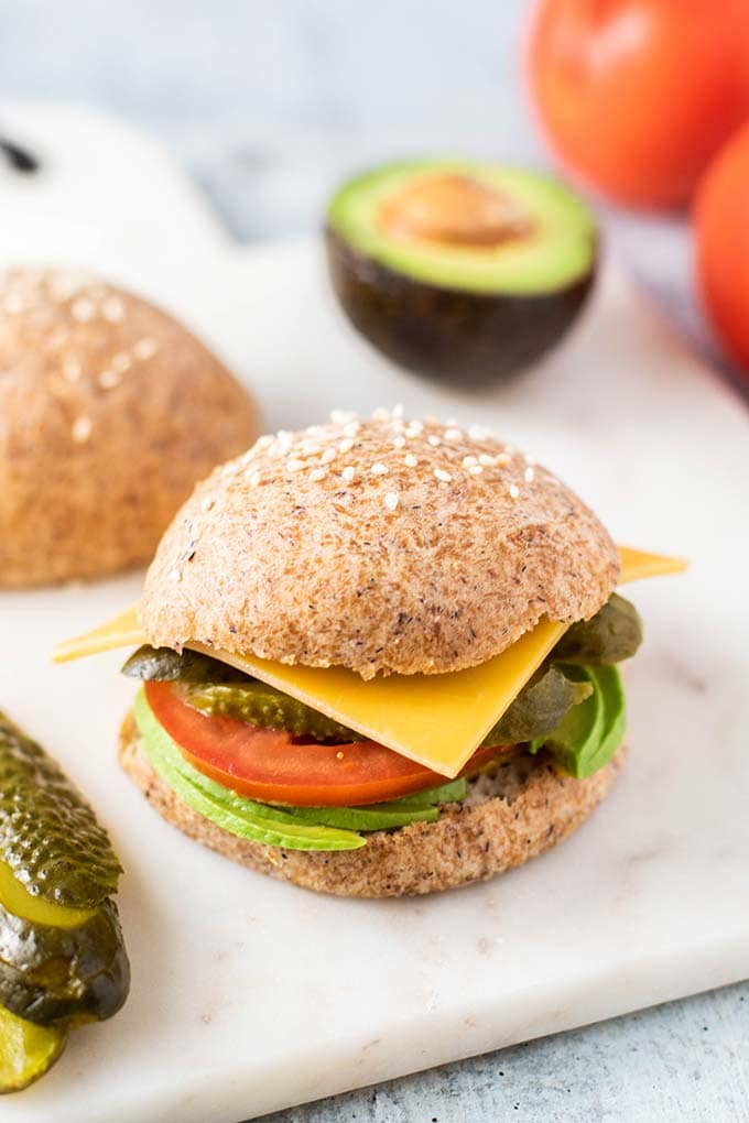 A sandwich with avocado, tomato, pickles, and cheese.