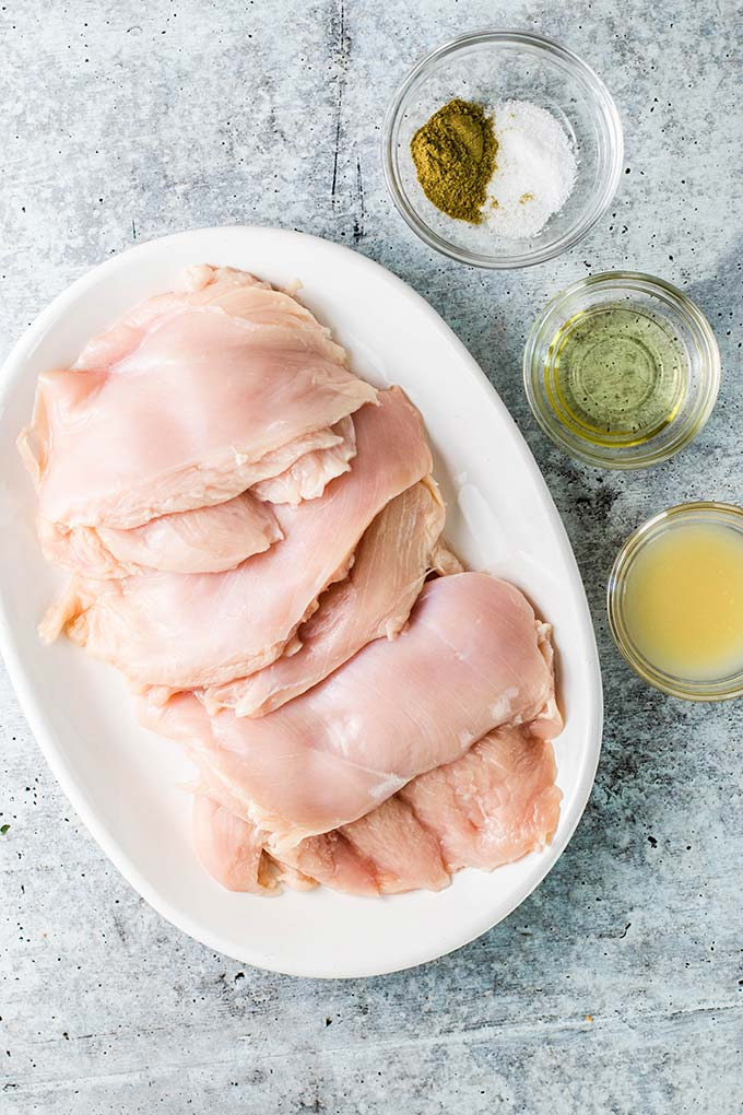 A plate of flattened chicken breasts next to the ingredients used to marinate the chicken.