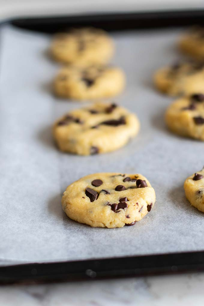 A baking tray with cookie dough, showing how to form cookies to bake.
