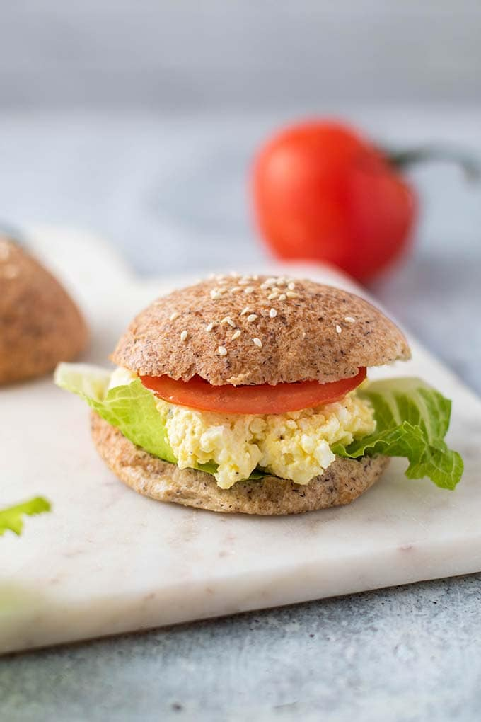 A sandwich on a keto bread roll with lettuce, egg salad, and tomato.