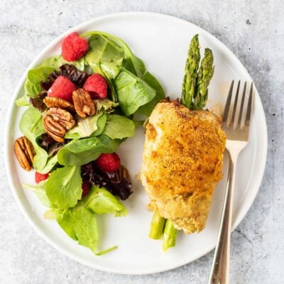A white plate with a green salad next to an asparagus stuffed chicken breast.
