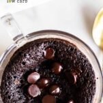 A close up of a chocolate mug cake with melted chocolate chips on top.