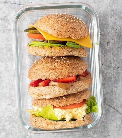 An egg salad sandwich, a cheese and vegetable sandwich, and an almond butter and strawberry sandwich, stacked in a glass meal prep container.