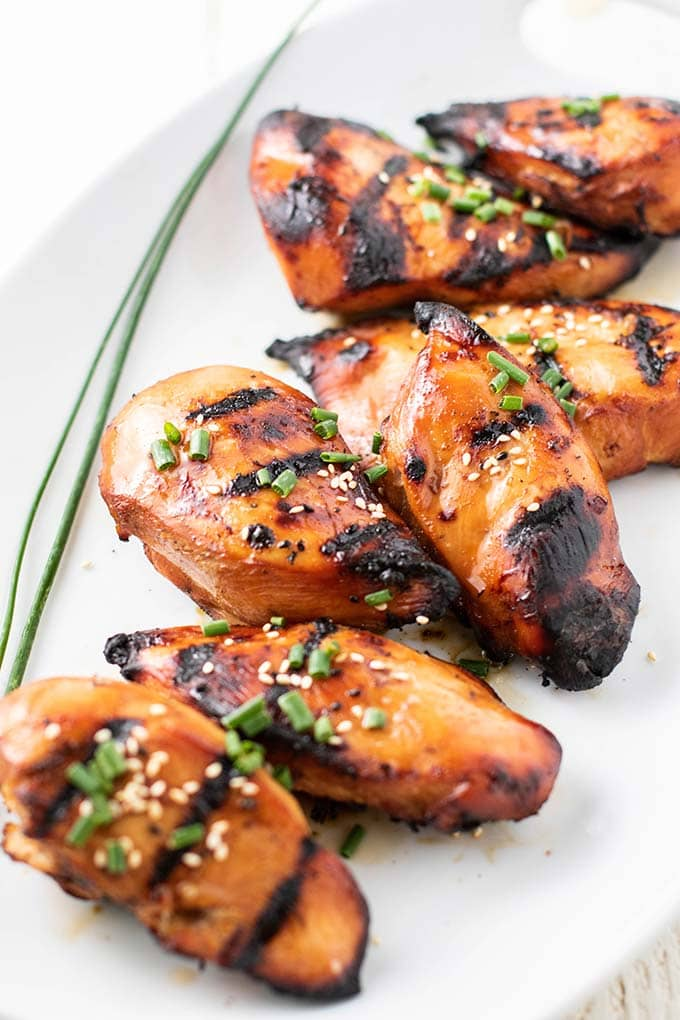 A platter of marinated chicken garnished with sesame seeds and green onions.
