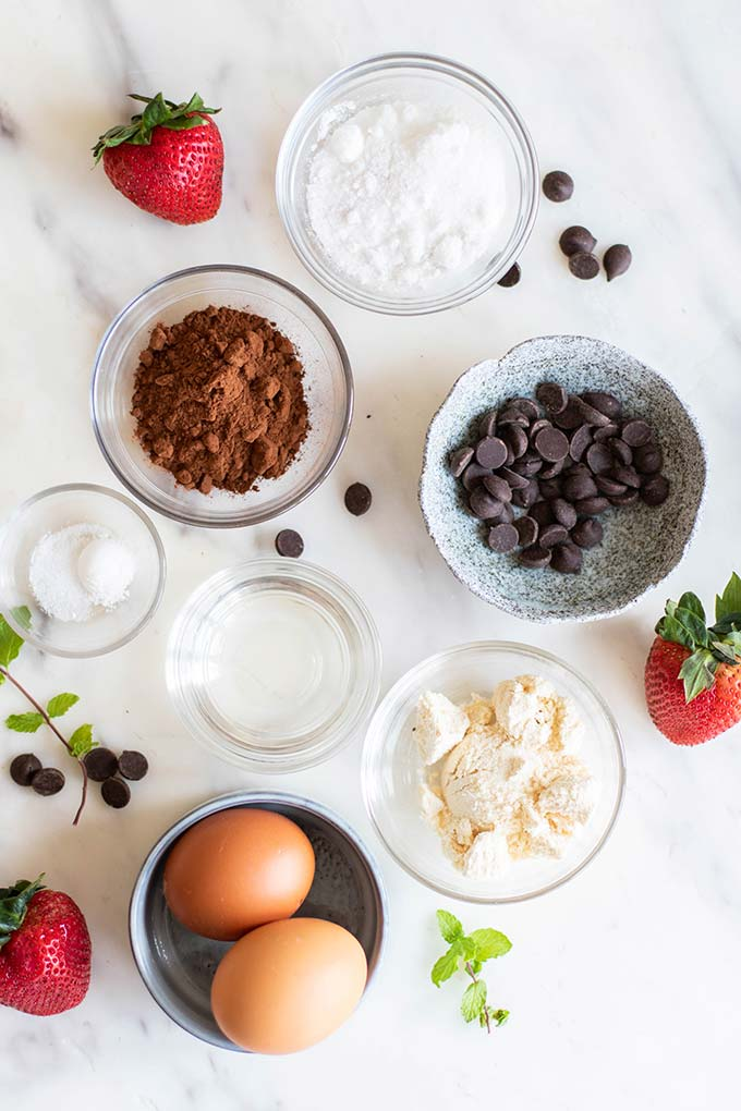 The ingredients for a keto chocolate mug cake in clear ramekins.