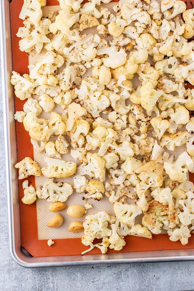 A roasting pan with lightly browned roasted cauliflower and garlic.