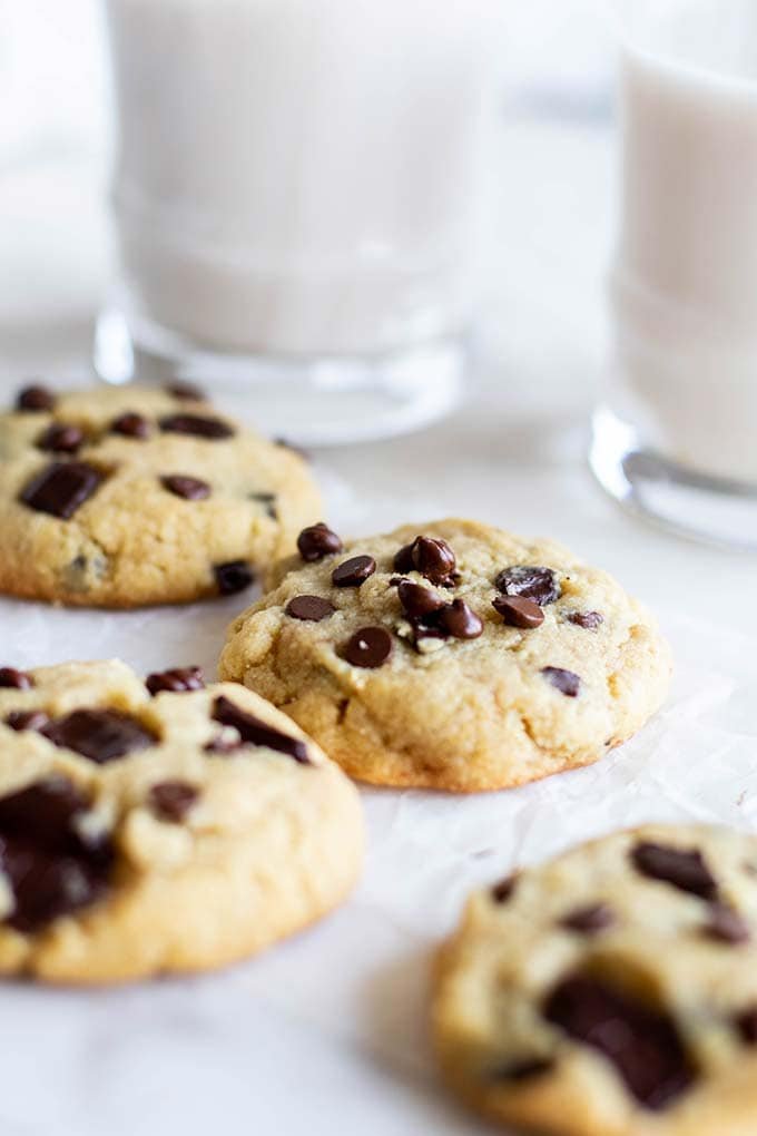 Several thick almond flour chocolate chip cookies in front of 2 glasses of milk.