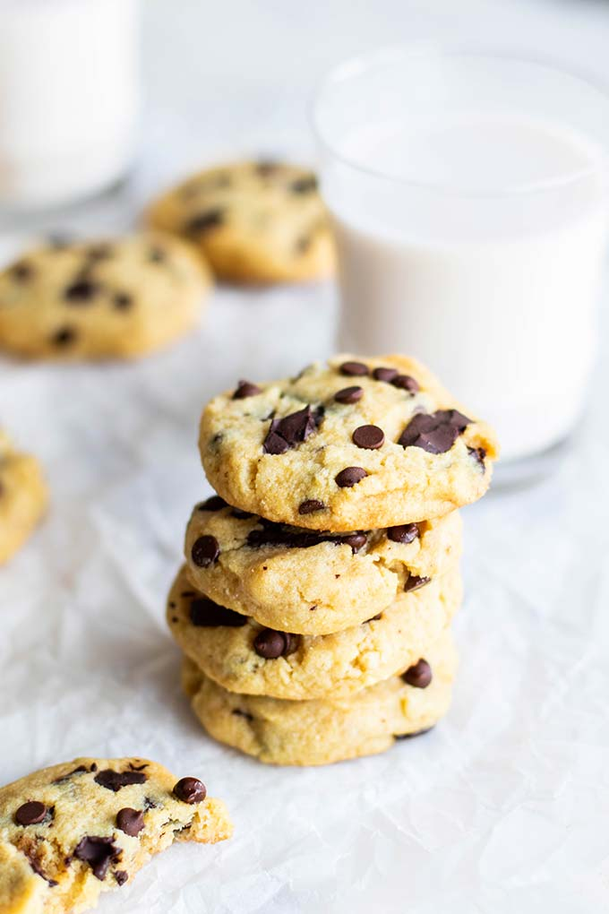 A stack of soft and chewy keto chocolate chip cookies in front of a glass of milk.