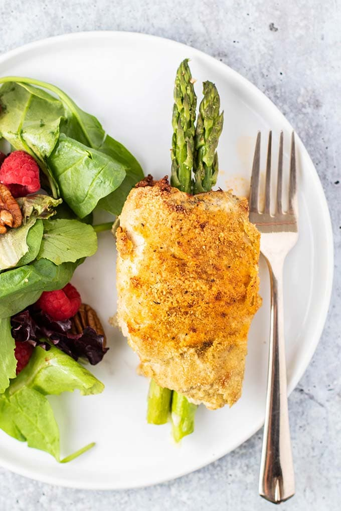 A stuffed chicken breast on a plate next to a salad.