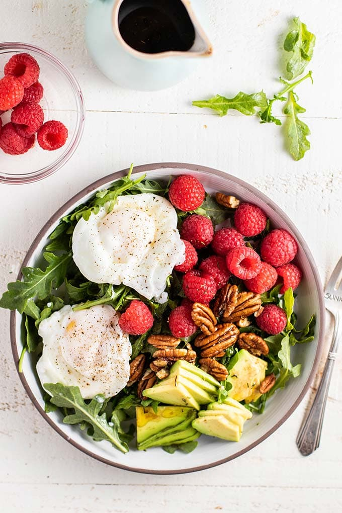 A keto breakfast salad topped with poached eggs, raspberries, pecans and avocado.