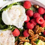 A close up look at an arugula salad with eggs, raspberries, avocados and pecans.