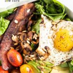 A close up look at a power greens salad with bacon, eggs, mushrooms and tomatoes.