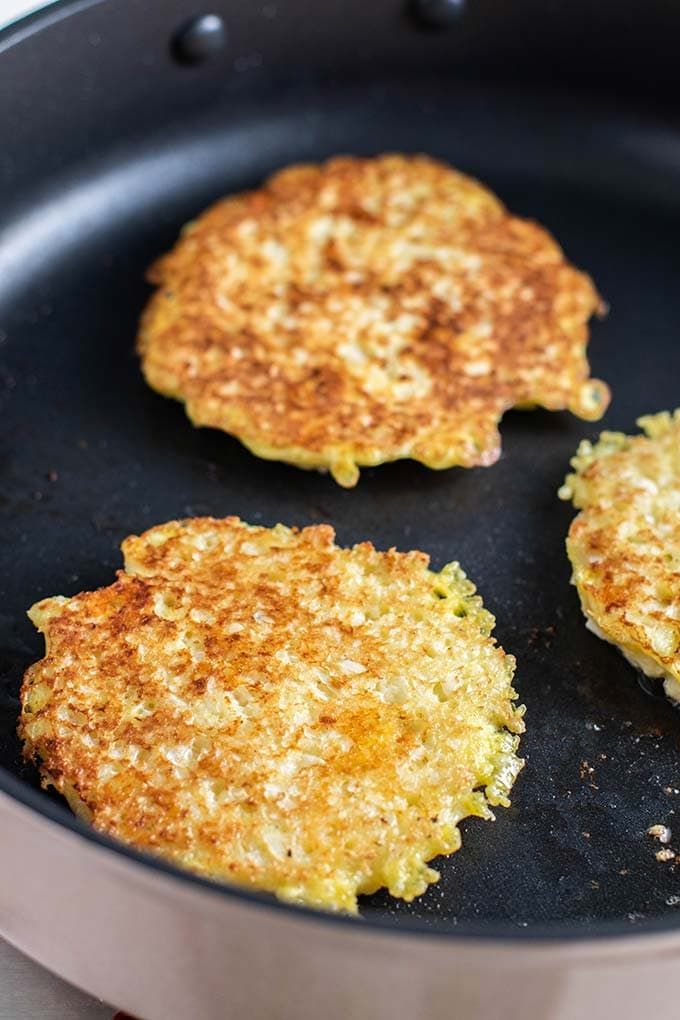 Cheesy keto cauliflower fritters frying in a pan.