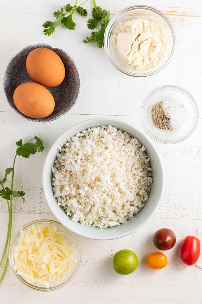 Cauliflower rice, eggs, cheese. salt and pepper, and almond flour, ready to be combined for this recipe.