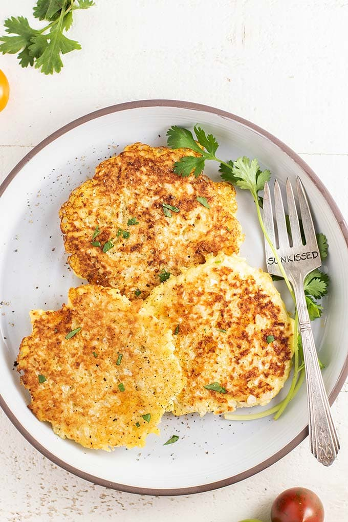Three crispy browned cauliflower fritters on a white plate.