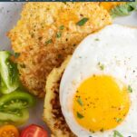 A close up look at cauliflower fritters topped with an egg, along with nutritional data.