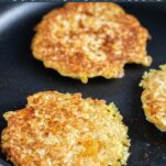 Cauliflower fritters frying in a pan.
