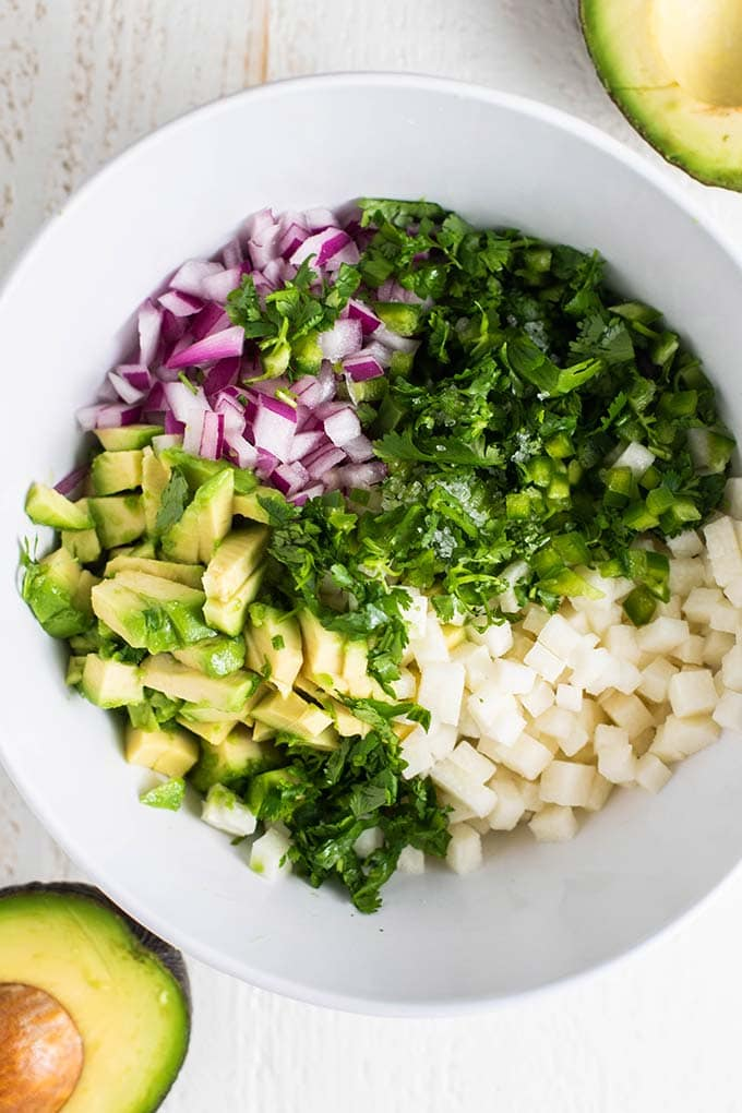 The ingredients for avocado salsa in a white bowl ready to be combined.