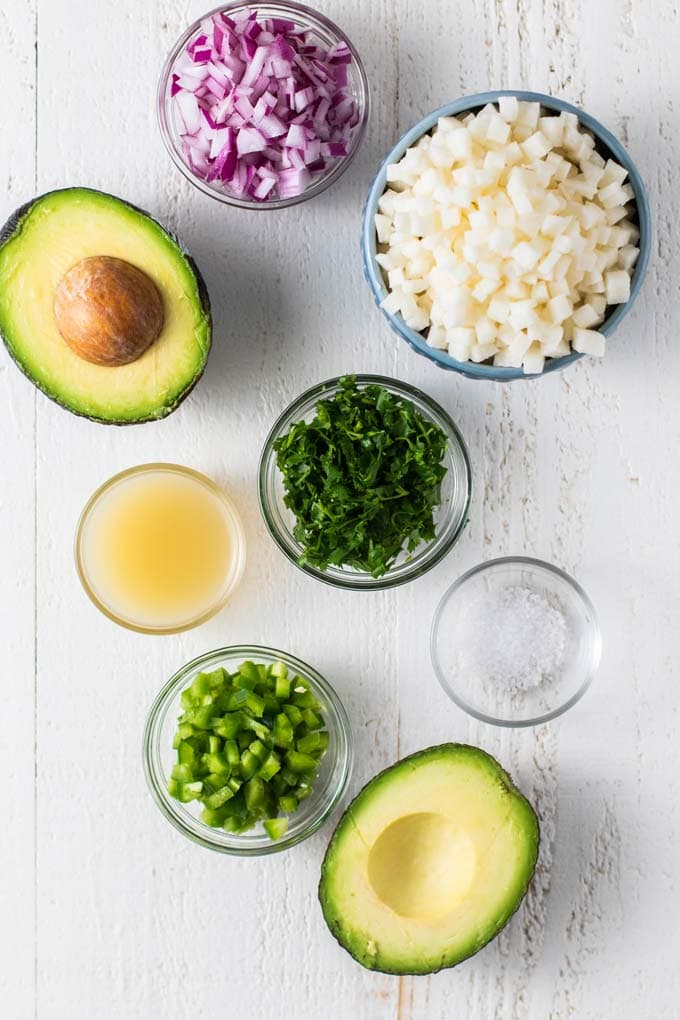 The ingredients for avocado salsa shown prepared and in dishes ready to be combined.
