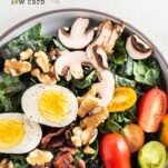 A close up look at a kale breakfast salad topped with eggs, bacon, mushrooms and tomatoes.