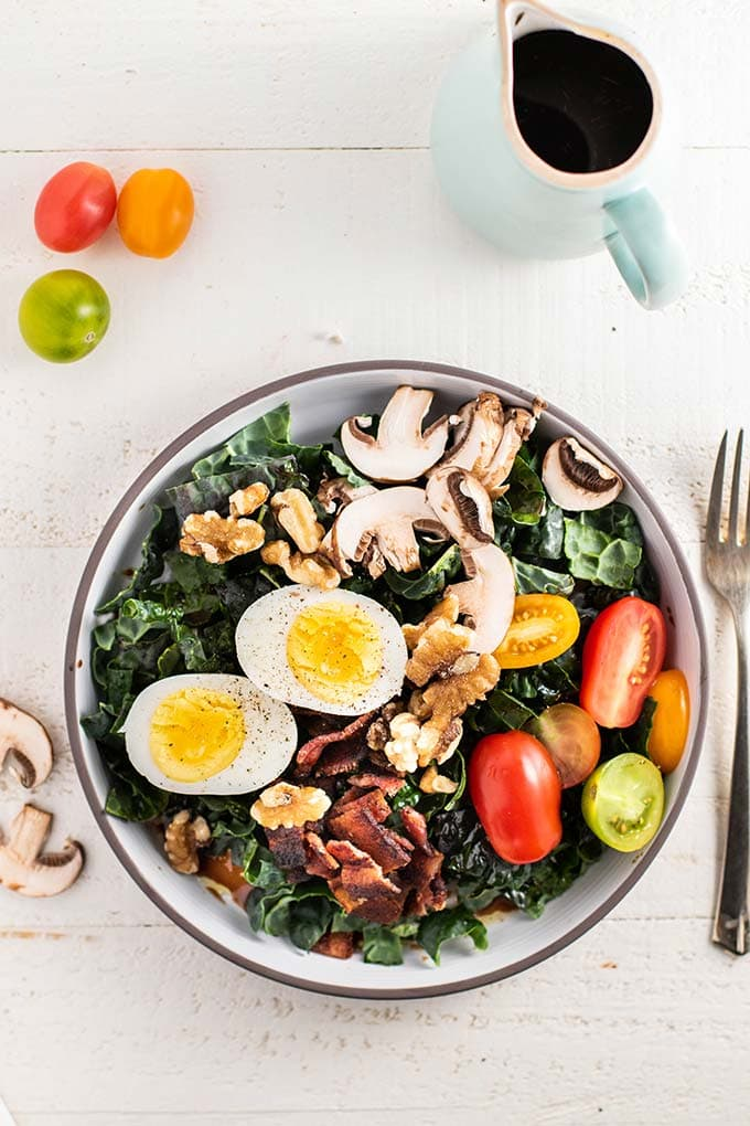 A kale keto breakfast salad with tomatoes, mushrooms, bacon and a hard boiled egg.
