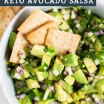 A close up look at almond flour crackers dipping up an avocado salsa.