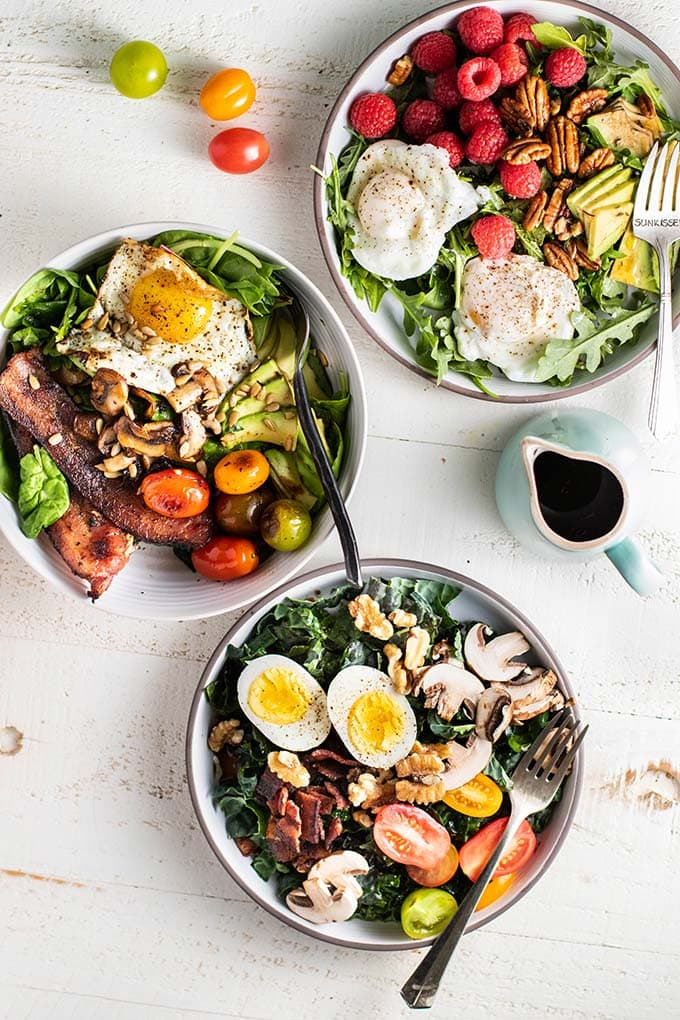 Three keto breakfast salads with a container of salad dressing.