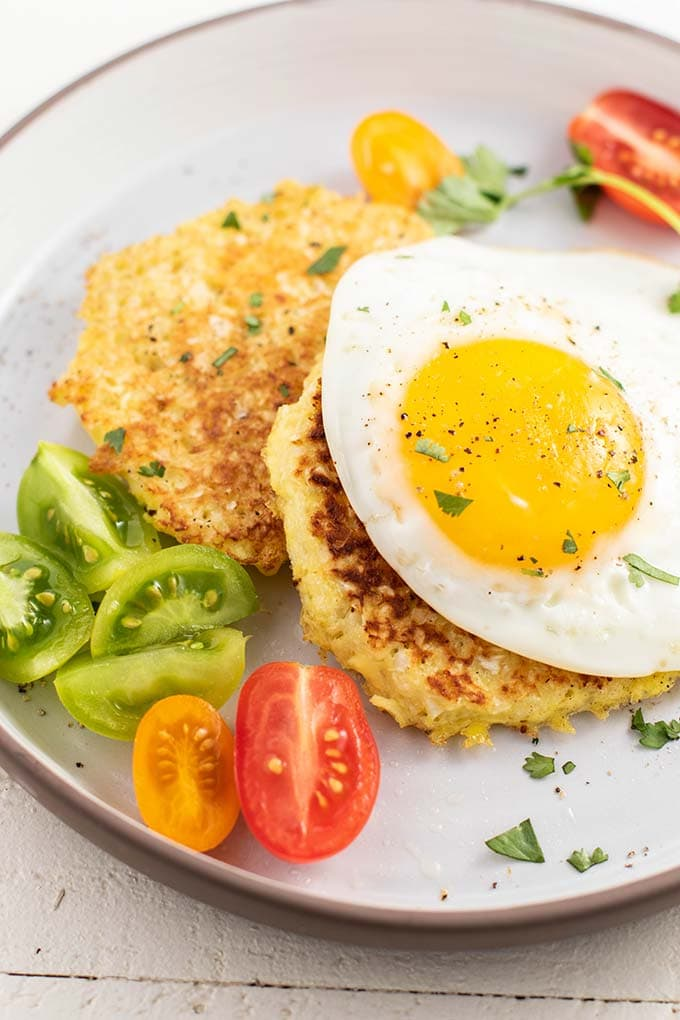 Two cauliflower fritters on a white plate served with tomatoes and an egg.