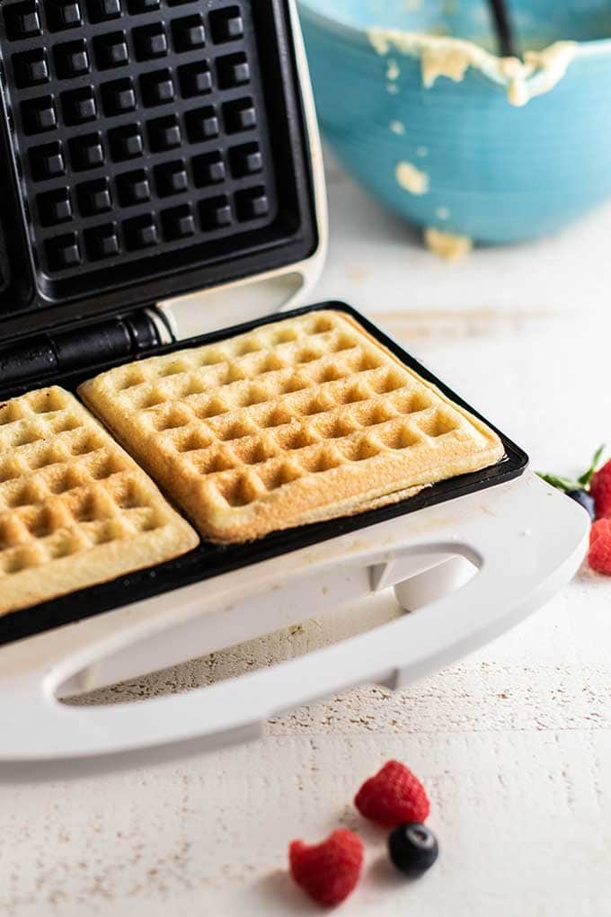 Almond flour waffles cooking in a waffle iron.