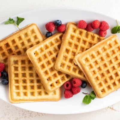 A plate with almond flour waffles surrounded by berries.