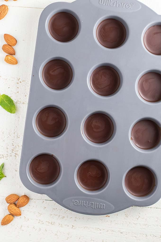 A silicone mini muffin pan with dark chocolate filling each cavity.