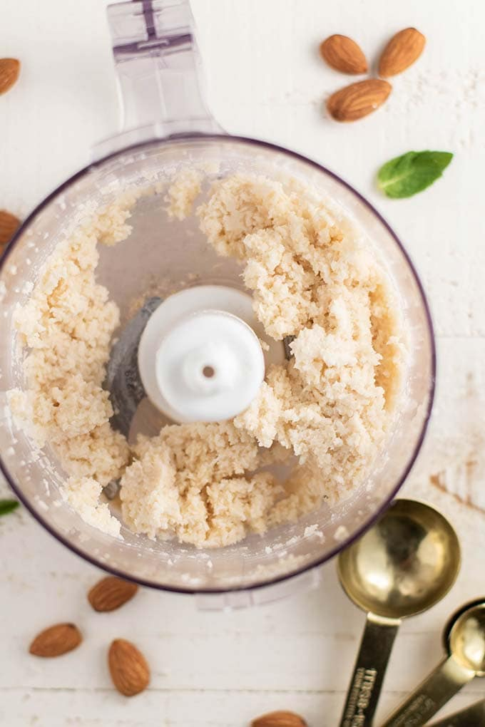 A food processor bowl showing the texture of the coconut filling.