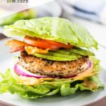 A turkey burger with avocado between two chunks of lettuce.