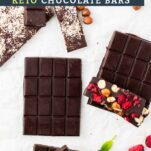 Three dark chocolate bars, one plain, one with raspberries and hazelnuts, and one with toasted coconut.