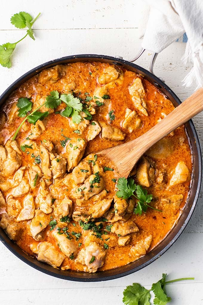 A black skillet filled with a saucy keto butter chicken garnished with cilantro.