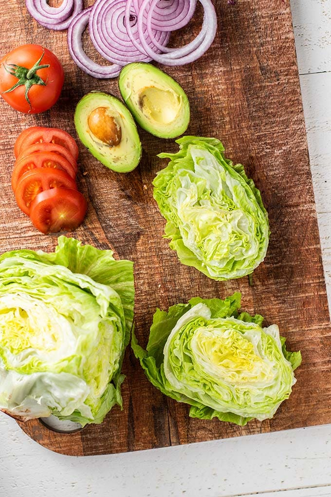 A cutting board with lettuce, tomatoes, onions, and avocado.