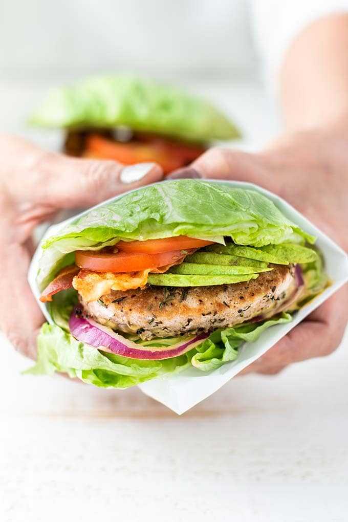 Hands holding a turkey burger wrapped in lettuce.