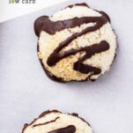A close up look at 2 macaroons drizzled with dark chocolate.