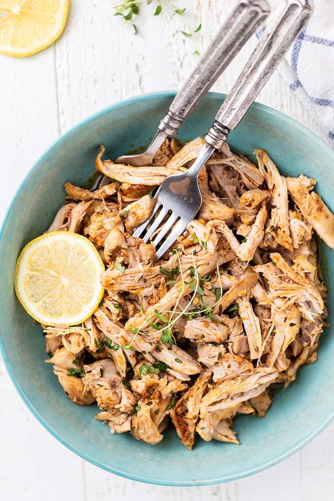 A blue bowl with shredded chicken thighs, garnished with thyme and lemon slices.