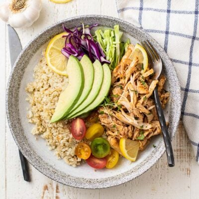 A white plate with cauliflower rice, shredded instant pot chicken thighs, tomatoes, cabbage and avocado.