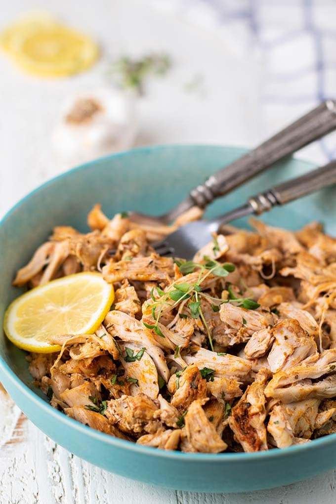 A side view of a bowl with shredded chicken thighs.