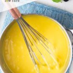 A whisk in a pan of lemon curd.