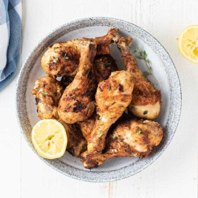 A plate of fried chicken legs with lemons and thyme.