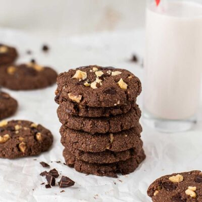A stack of keto double chocolate chunk cookies next to a glass of milk.