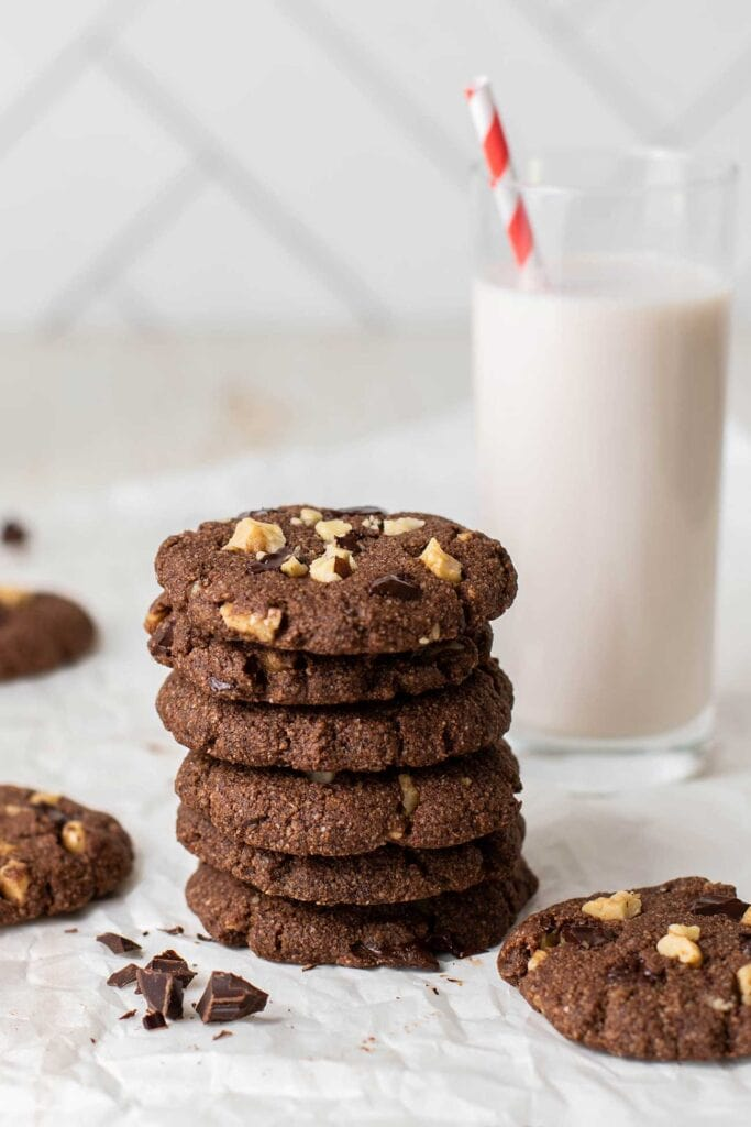 A stack of keto chocolate cookies next to a glass of milk.
